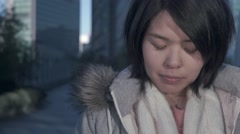 Slow-motion shot of young Japanese girl looking at camera with a serious look Stock Footage