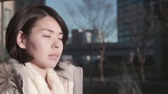 Slow-motion shot of young Japanese girl looking away with a serious look Stock Footage