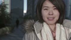 Slow-motion shot of young Japanese girl smiling at camera in Tokyo Stock Footage