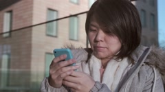 Slow-motion shot of smiling young Japanese girl texting on her smartphone Stock Footage