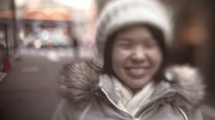 Slow-motion shot of young Japanese girl smiling at camera waving her hand Stock Footage