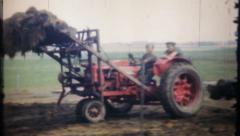 87 - farm tractor loads manure into horse drawn spreader-vintage film home movie Stock Footage