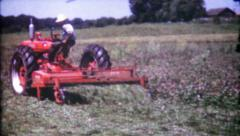 136 - farmers cutting grass in the fields with tractor - vintage film home movie Stock Footage