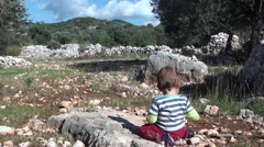 Small boy sits on the ground in Lycian forest 2 Stock Footage