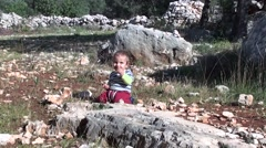 Small boy sits on the ground in Lycian forest zoom in Stock Footage