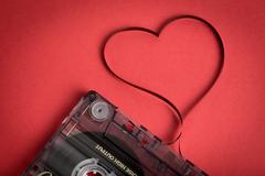 Audio cassette tape on red backgound. Film shaping heart - stock photo