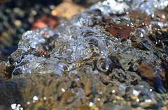 Macro photo of flowing bubbly river water on a sunny summer day - stock photo