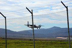 airplane coming in for landing on airport airstrip behind fence - stock photo