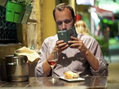 Young man taking photo of food with cellphone sitting in cafe at night NTSC Stock Footage