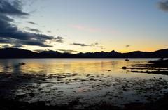 Beautiful colours behind mountain range and in fjord as the sun is going down Stock Photos