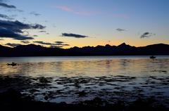Colourful sky, mountain and fjord as the sun is going down for the night Stock Photos