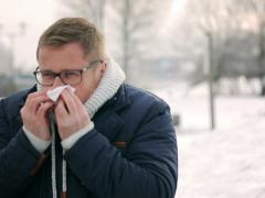 Man standing in the park at winter time and blowing nose Stock Footage