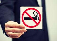 man in suit holding no smoking sign - stock photo