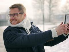 Happy man doing selfie on tablet in the snowy park Stock Footage
