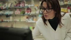 Good looking Pharmacist woman checking prescription medicines at the pharmacy Stock Footage