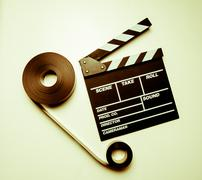 Two 35mm movie reels and clapperboard in vintage color effect - stock photo