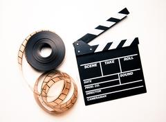Unrolled 35mm movie reel and clapperboard in vintage color effect Stock Photos