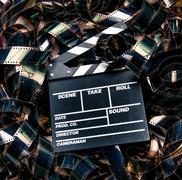 Unrolled heap 35mm movie filmstrip color carpet and clapperboard - stock photo