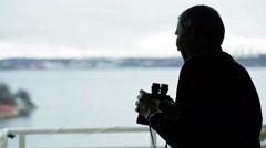 Old man looking in a binocular Stock Footage