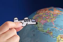 Airplane flies against the globe - stock photo
