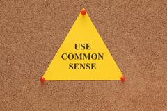 "Triangular paper note with the words ""use common sense"" - stock photo"