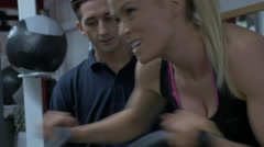Spin bike woman 20's with Personal trainer Stock Footage