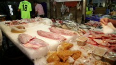 Fresh fish display with vendor and customer transaction across shot Stock Footage