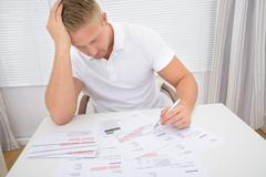 Portrait Of A Worried Man Calculating Unpaid Bills - stock photo