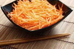 Grated carrots in bowl with chopsticks - stock photo