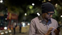 Young, trendy man standing with smartphone in the city at night HD Stock Footage