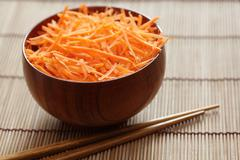 Grated carrots in bowl with chopsticks Stock Photos