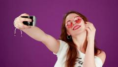 Funny fashion girl in pink round glasses make selfie on purple background Stock Footage