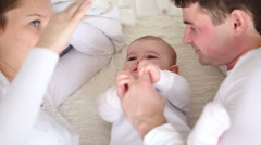 Young parents playing with baby on the bed Stock Footage
