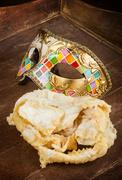 Fried pastry of italian carnival with venetian mask. Stock Photos
