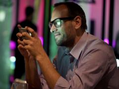 Young man plying game on smartphone sitting in cafe at night NTSC Stock Footage