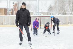 A family playing at the skating rink in winter Stock Photos