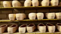 Rows of unfinished clogs on a shelf Stock Footage