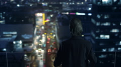 Businessman on the Roof is Looking at Night City Stock Footage