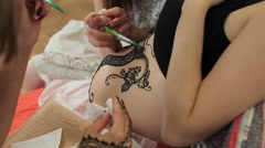 Process of applying Mehndi on the abdomen of a pregnant woman Stock Footage