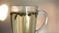 Hot water over tea in transparent glass cup Stock Footage