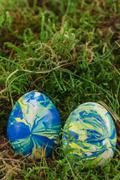 Two Easter eggs lying in the moss Stock Photos