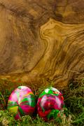 two easter eggs in moss with wood background - stock photo