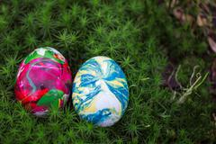 two Easter eggs lying in the moss - stock photo