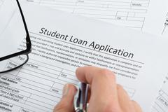 Close-up Of Hand Holding Pen Over Student Loan Application Stock Photos