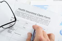 Close-up Of Hand Holding Pen Over Health Insurance Claim Application Form - stock photo