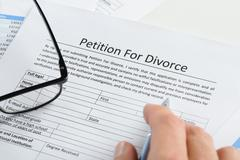 Close-up Of Hand With Pen On Petition For Divorce Paper Stock Photos