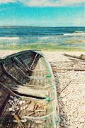 Old wooden boat on the seashore, retro image - stock photo