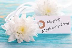Label with white Flowers on turquiose Board with Happy Mothers Day on it - stock photo