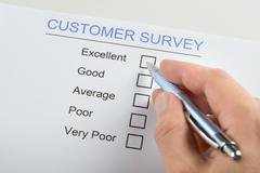 Stock Photo of Close-up Of Person Hand Filling Customer Survey Form With Pen