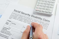 Person Hand With Pen Filling Social Security Disability Form - stock photo